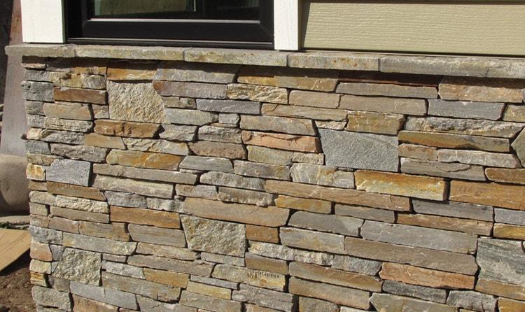 Облицовка фасада искусственным камнем - фото частного дома