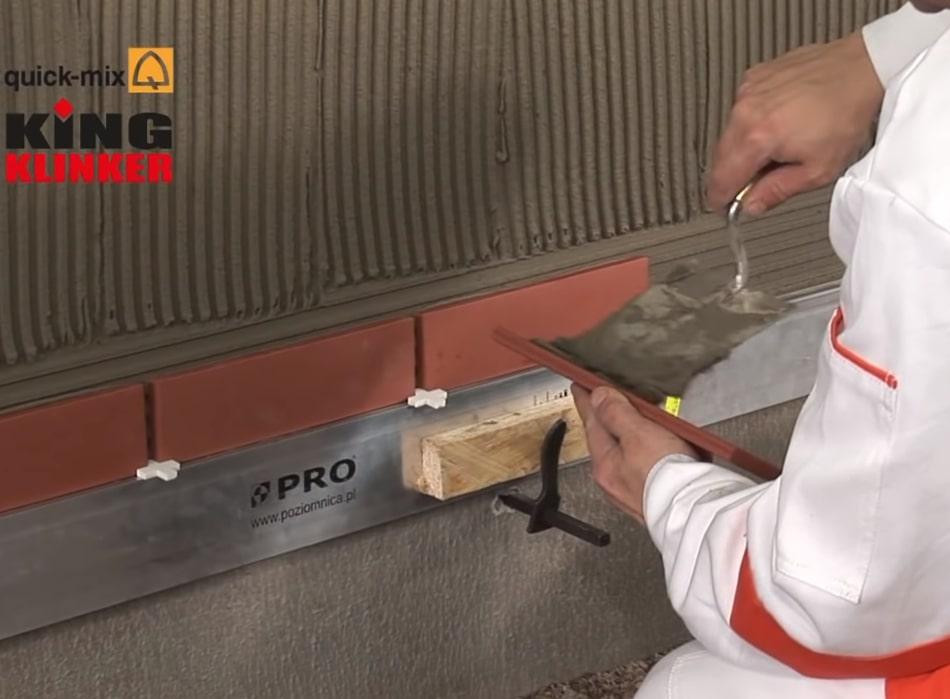 Нанесение клинкерной плитки на клеевой состав стены